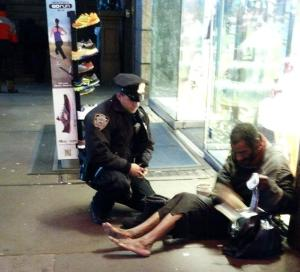 NYPD policeman Larry DePrimo gives boots to a homeless man
