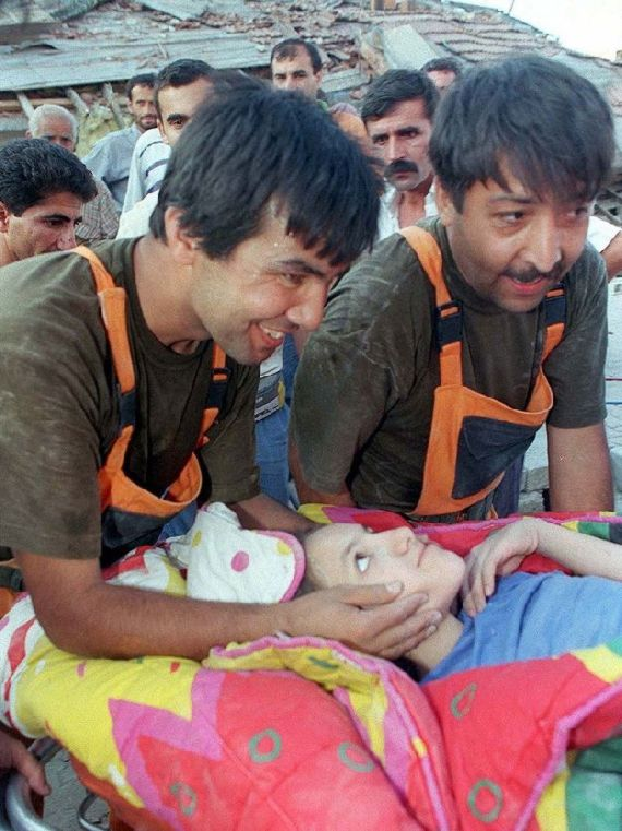 Rescuers Smile while Carrying Girl from Rubble